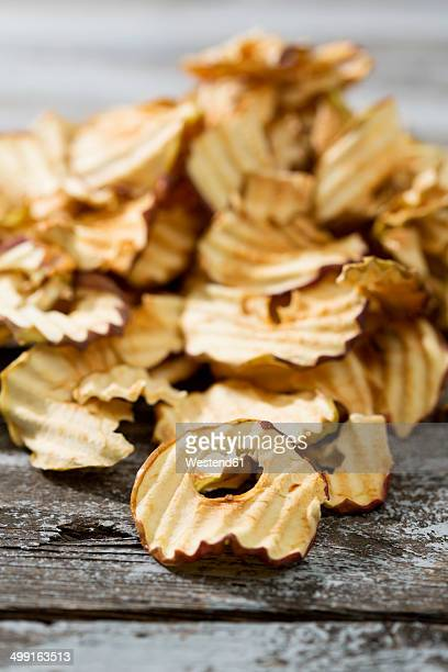 Pile of dried apple rings on grey wooden table