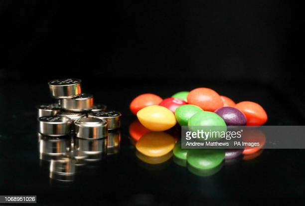 A pile of Energizer LR44/A76 Alkaline 15v batteries next to a pile of Skittles sweets
