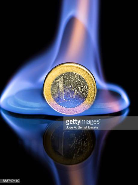Pile of euro coins burned by the fire of the crisis