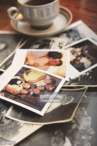 Pile of family photographs on table, next to tea cup