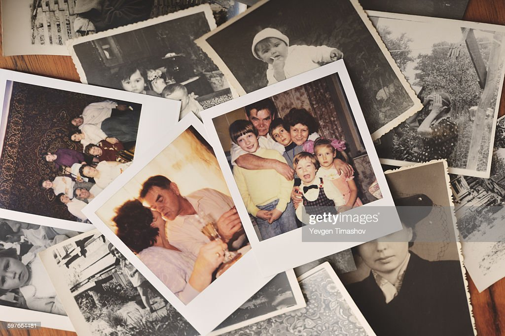 Pile of family photographs on table, overhead view : Stock Photo