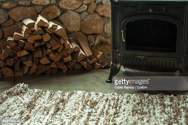 Pile Of Firewood By Stove By Rug At Home