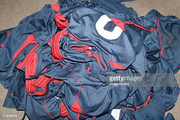 pile of football uniforms - sports uniform stock pictures, royalty-free photos & images