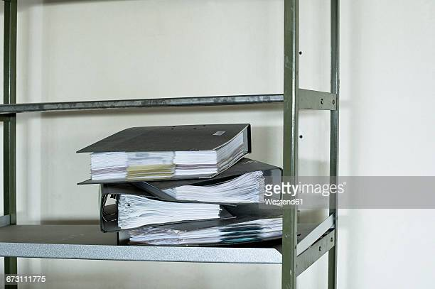 Pile of four office files on a shelf