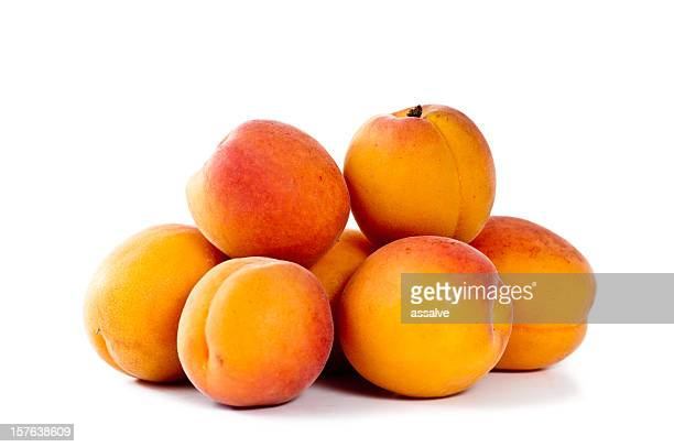 A pile of fresh apricots on a white background