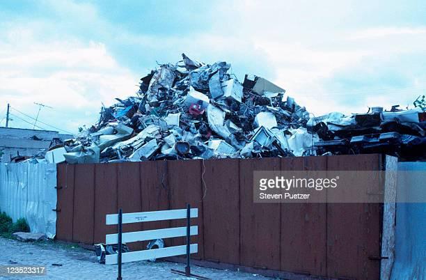 pile of garbage behind fence - ferro velho imagens e fotografias de stock