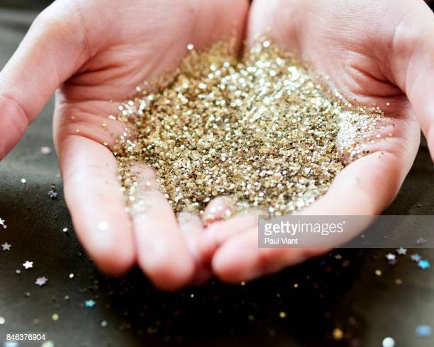 Pile of gold glitter in woman's palm