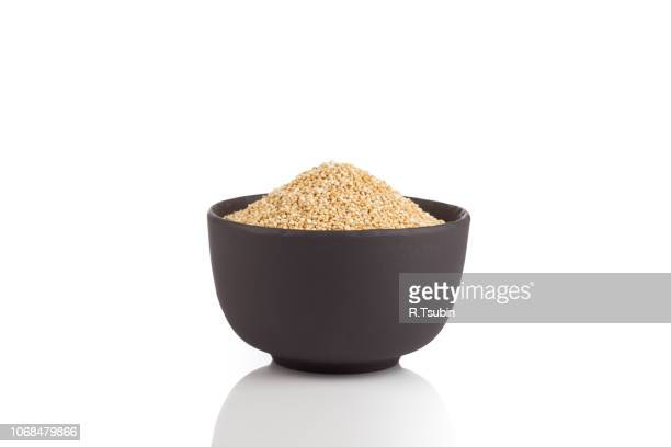 pile of grain quinoa seeds in bowl isolated over the white background - quinoa stock pictures, royalty-free photos & images