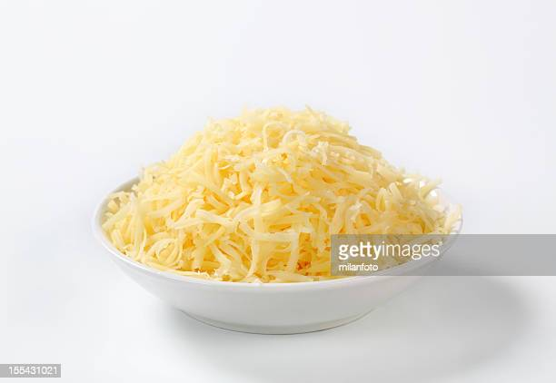 A pile of grated cheese in a white bowl on white background