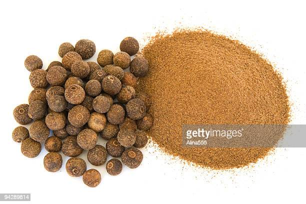 Pile of ground and whole allspice on white
