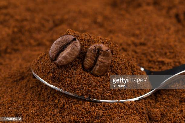pile of ground coffee and a metal spoon close up - café moulu photos et images de collection