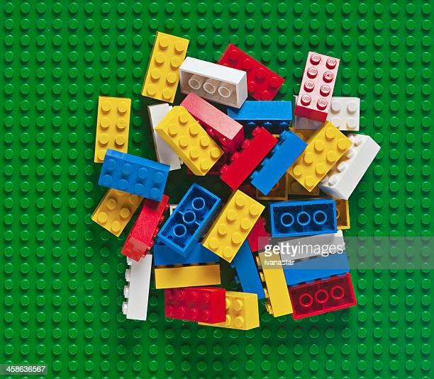 pile of lego block bricks on green baseplate - lego stock pictures, royalty-free photos & images