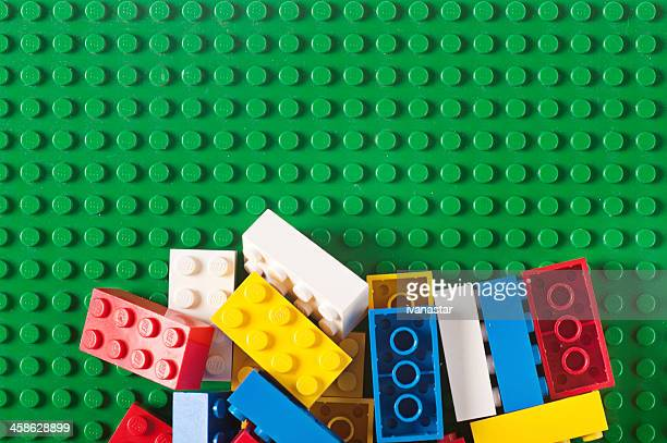 pile of lego blocks and bricks on green baseplate - lego stock pictures, royalty-free photos & images