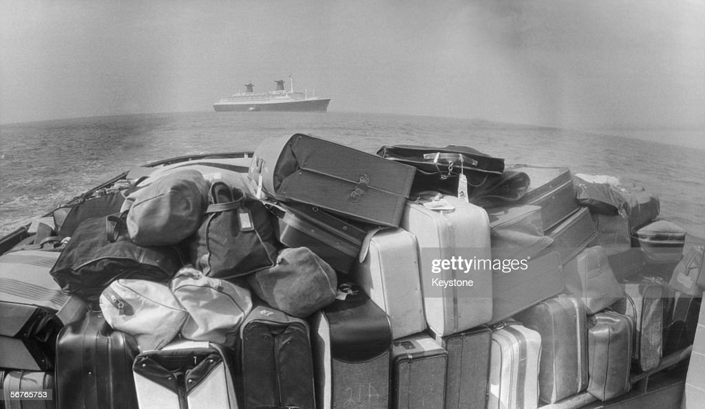 pile-of-luggage-on-the-deck-of-a-tugboat-being-transported-from-the-picture-id56765753