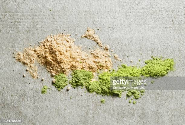 a pile of maca powder and barley sprouts powder (seen from above) - maca plant stock photos and pictures