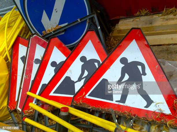 pile of men at work signs - detour sign stock photos and pictures