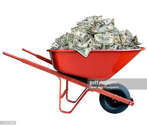 pile of money in wheel barrow - wheelbarrow stock photos and pictures