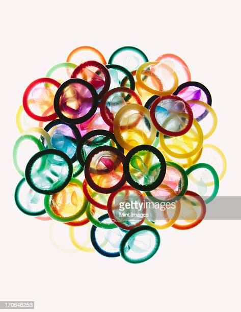 A pile of multi-colored condoms on a white background.