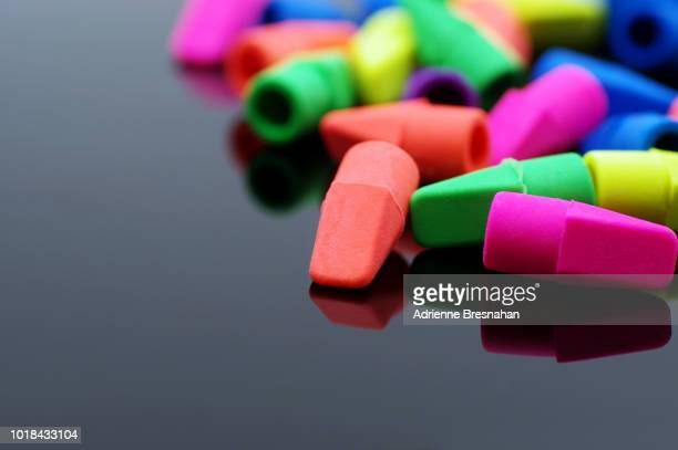 Pile of Neon Colored Erasers on Black Backdrop With Copy Space