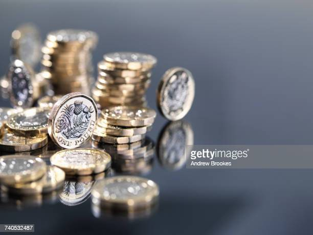 pile of new british one pound coins, close-up - money stock photos and pictures