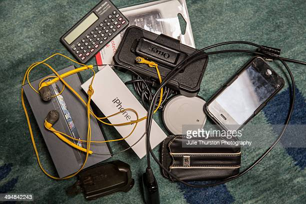 Pile of Obsolete Electronic Technological Waste Including Old Mobile Cell Phone Cases Calculator iPhone and Box Headphones Cords and Cables