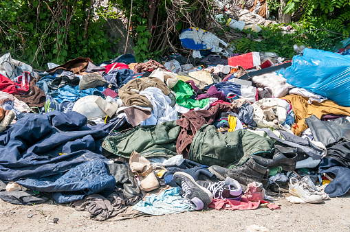 Pile of old clothes and shoes dumped on the grass as junk and garbage, littering and polluting the environment 957312514