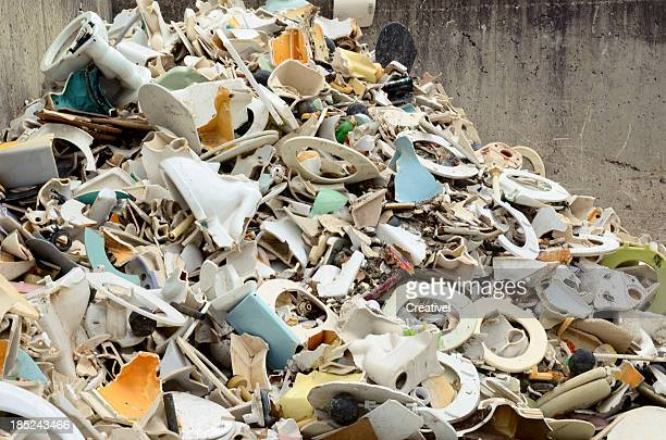pile of old toilets at garbage transfer station - landfill stock photos and pictures