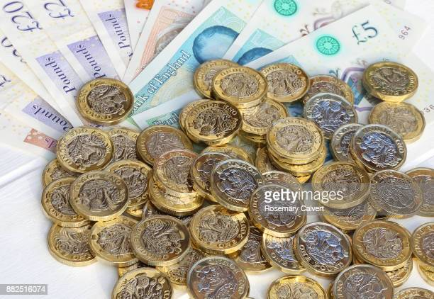 Pile of one pound coins in close-up with pound notes.