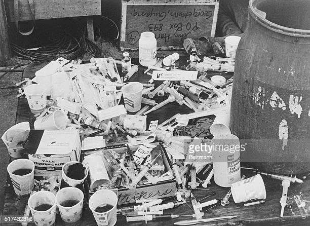 A pile of paper cups with cyanidelaced fruit punch and a pile of hypodermic syringes found at Jonestown by Guyanese officials