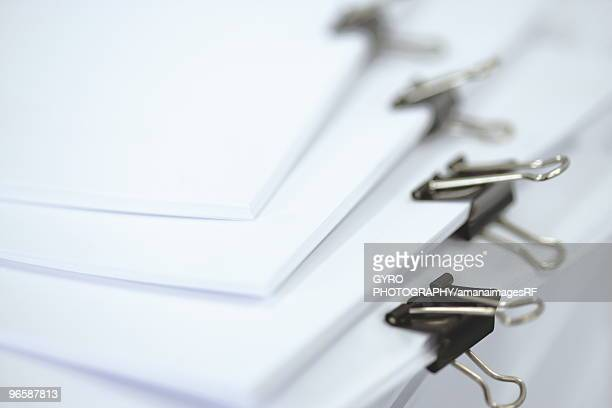 Pile of papers clipped together with binder clips