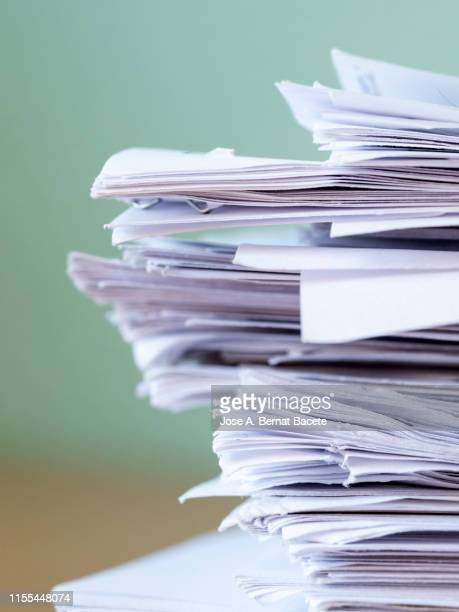 pile of papers on a work table. - equipamento à base de papel imagens e fotografias de stock