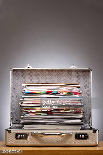 Pile of paperwork in open briefcase on desk