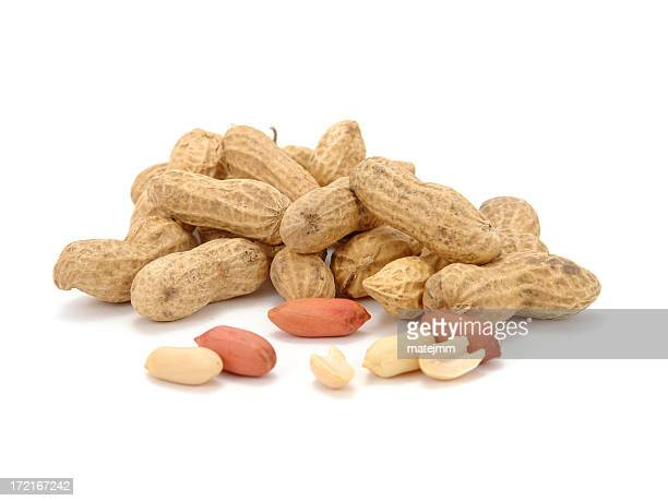 a pile of peanuts on a white background - peanuts stockfoto's en -beelden