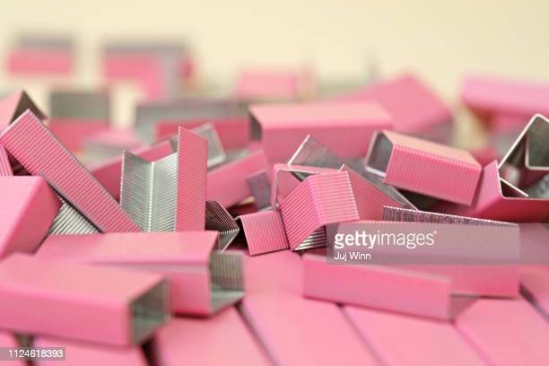 Pile of pink office staples on cream background with shallow depth of field