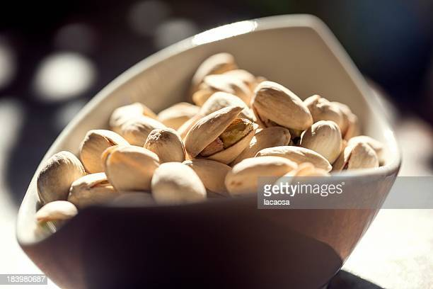 pile of pistachio nuts in white bowl