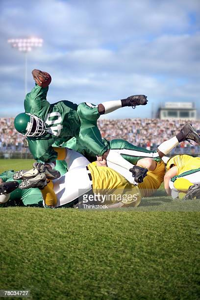 pile of players during football game - tackling stock pictures, royalty-free photos & images