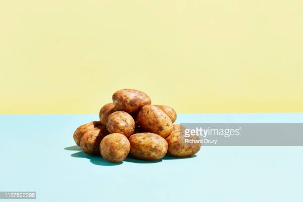 a pile of potatoes on a table top - rauwe aardappel stockfoto's en -beelden