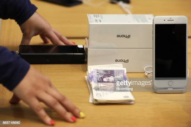 A pile of pound sterling banknotes sits on a cash desk as payment for two iPhone X smartphones at the Apple Inc store on Regent Street in London UK...
