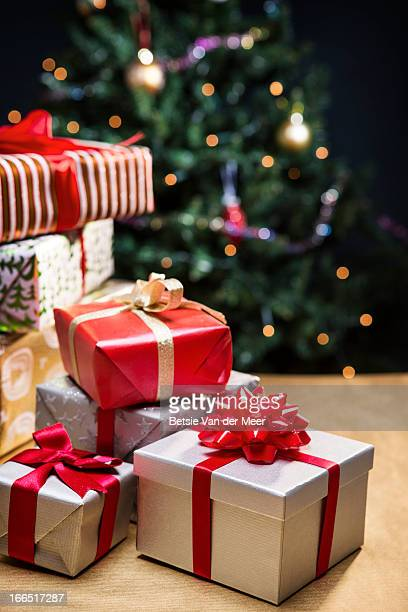 Pile of presents in front of christmas tree.