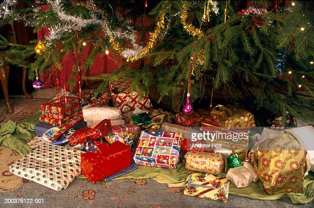 Pile of presents on floor beneath Christmas tree, close-up