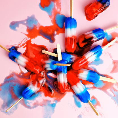 A pile of red, white, and blue ice pops in a melted puddle. - gettyimageskorea