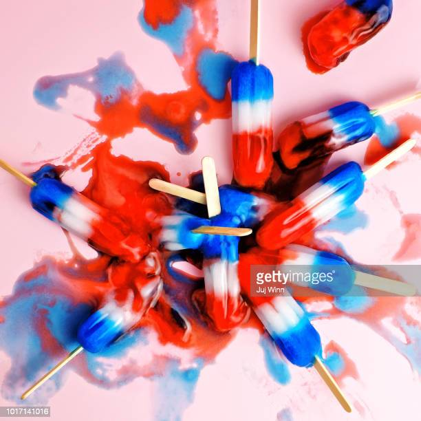 A pile of red, white, and blue ice pops in a melted puddle.