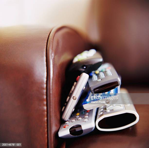 Pile of remote controls on sofa, close up