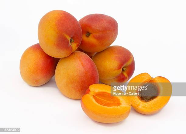 A pile of ripe apricots, one halved
