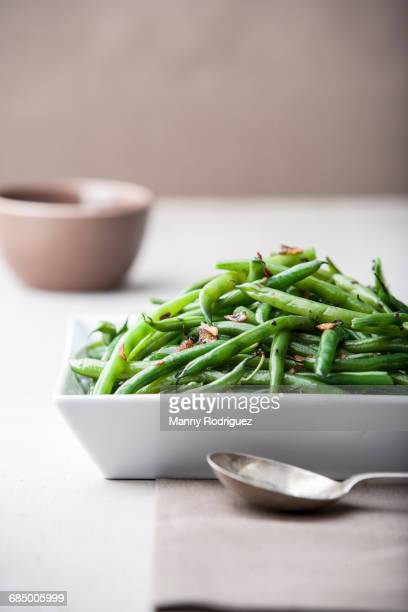 Pile of roasted green beans with spoon