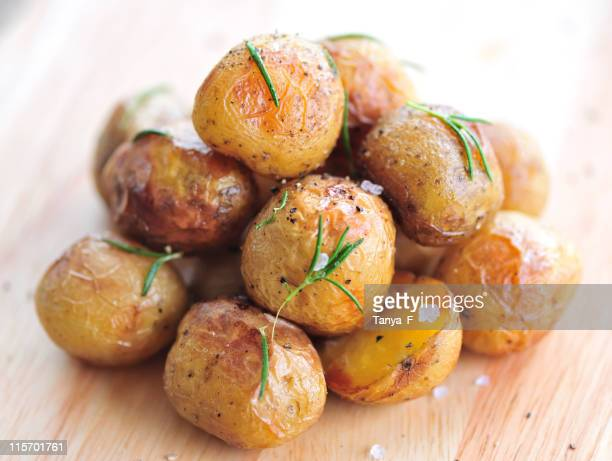 A pile of roasted young potatoes on a wooden table