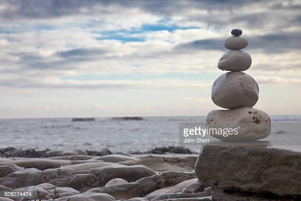 Pile of rocks balanced on a boulder at the water's edge; south shields tyne and wear england