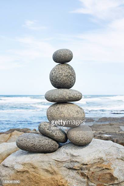 a pile of rocks balancing, sea in background - pietra roccia foto e immagini stock