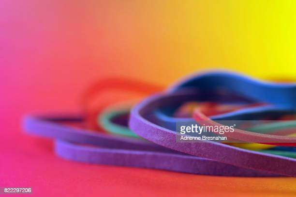 Pile of Rubber Bands on Rainbow Background