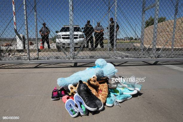 A pile of shoes and a teddy bear are seen in front of a fence where private security along with a Department of Homeland Security Police officer...